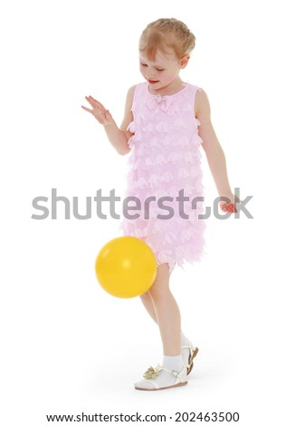 Girl in pink dress playing with a yellow ball.ball game,active lifestyle,happiness concept,carefree childhood concept. - stock photo