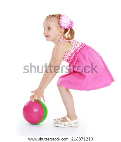 Girl in pink dress plays with a ball on a white backgroundConcept of childhood and family values. - stock photo