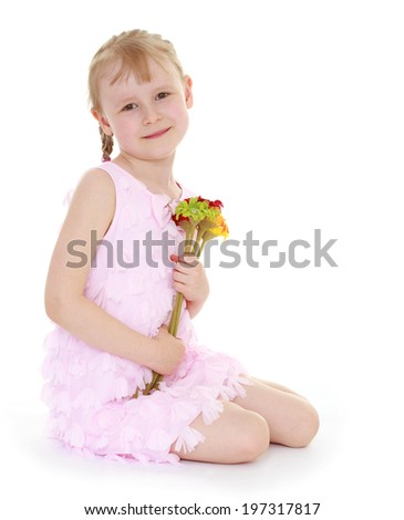 Girl in pink dress sitting on the floor with a bouquet of flowers
