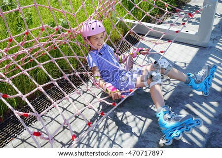 Girl in pink helmet and rollers sits in net hammock in skate park at summer
