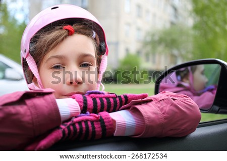 Girl in pink helmet leaning on the open window in the car - stock photo