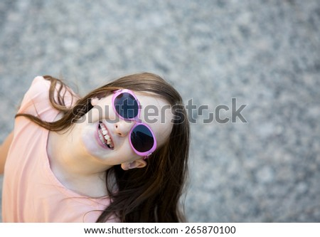 Girl in pink shirt looks happily up at the camera with funky pink sunglasses on.