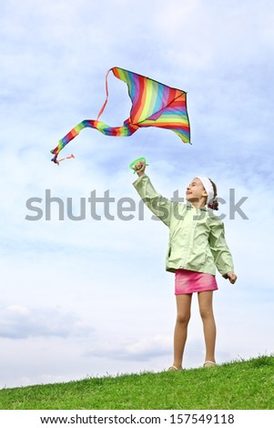 Girl in pink skirt and green jacket launches colorful kite on blue sky with clouds