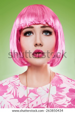 Girl in pink wig and dress with candy posing in studio - stock photo