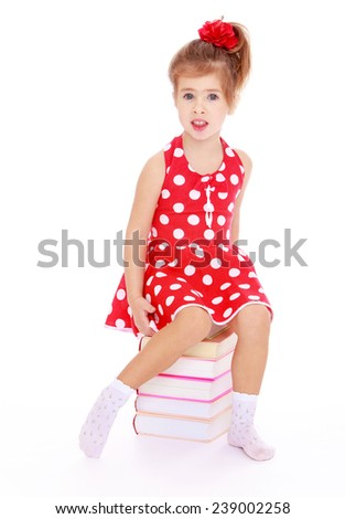 Girl in polka-dot dress sitting on a pile of books. Studio photo, isolated on white background. - stock photo