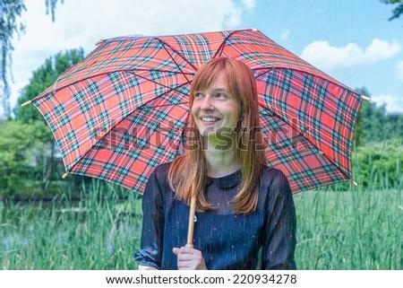 Girl in rain under umbrella with nature background - stock photo