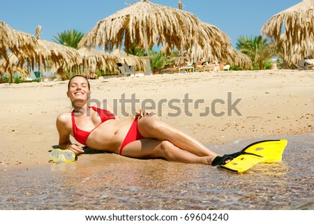 girl in red bikini with mask and flippers on beach - stock photo