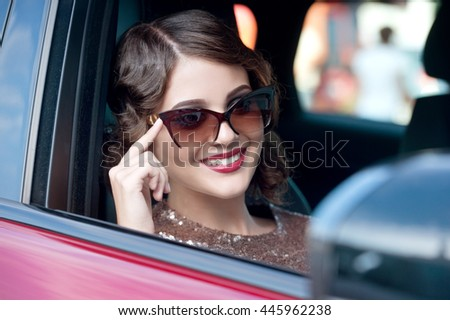 Girl in red car. Beautiful young woman retro style.