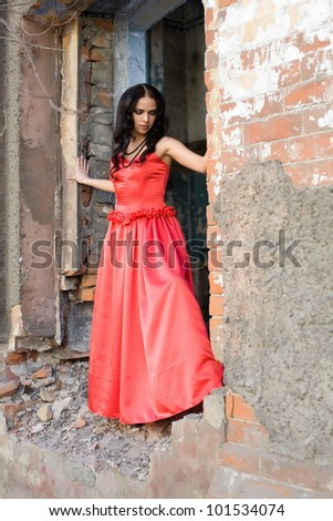 girl in red dress in the opening window of a ruined house