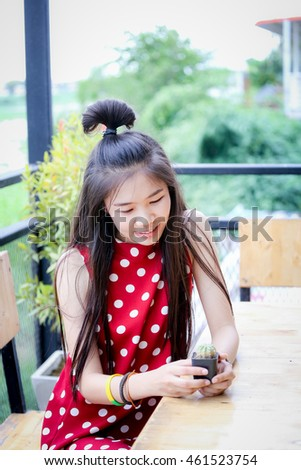 girl in red dress , she sit and have cactus in her hand