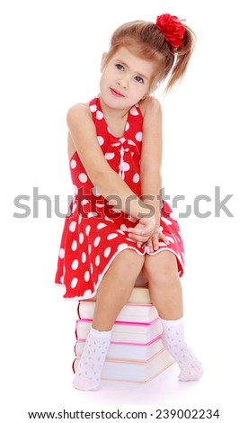 Girl in red dress sitting on a pile of books. Studio photo, isolated on white background. - stock photo