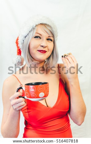 girl in red dress with big Breasts holding a red Cup of hot drink in the other hand cookies with chocolate chips