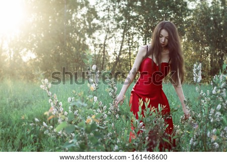 Girl in red dress with white fluffy flowers - stock photo