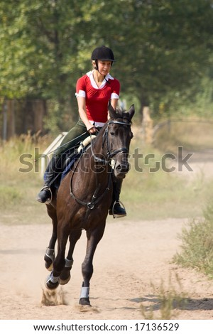 Girl in red t-shirt on riding horse - stock photo