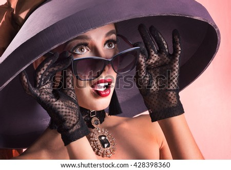 Girl in retro - hat and sunglasses. She wondered what she saw. - stock photo