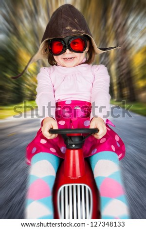 Girl in retro racing hat and goggles driving on toy car at speed with blurred background.