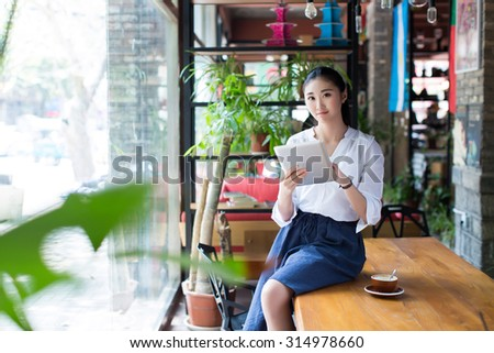 girl in romantic cafes, sipping strong coffee and her tablet computer - stock photo