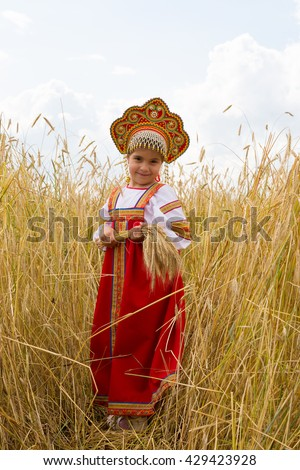 Girl in Russian national sarafan and a kokoshnik standing in a wheat field in summer day