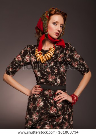 Girl in Russian style posing in red kerchief and bagels on the neck.