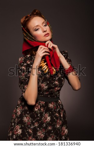 Girl in Russian style posing in red kerchief and bagels on the neck. Tying a red scarf.