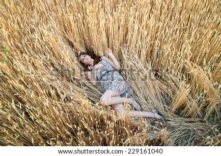 girl in rye field. girl lies on an ear of wheat. Wheat field. spikelet - stock photo