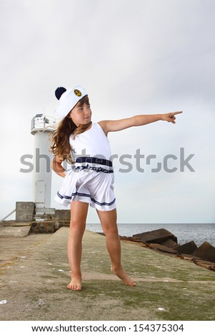 Girl in sailor costume stands on stone breakwater and points to the sea - stock photo