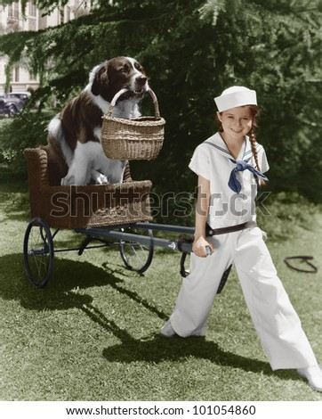 Girl in sailor suit pulling dog in basket - stock photo