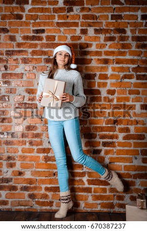Girl in santa hat holding a gift on New Year's, standing on one leg in woolen socks