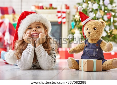 girl in Santa hat playing with teddy - stock photo
