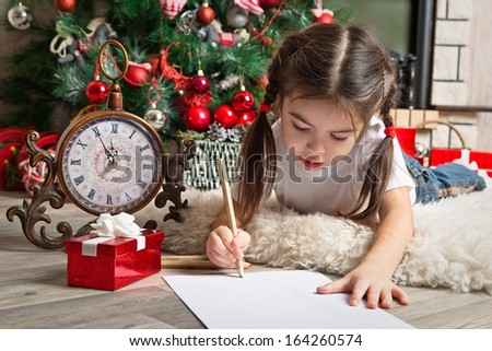 Girl in Santa hat writes letter to Santa Claus near christmas tree and clock - stock photo