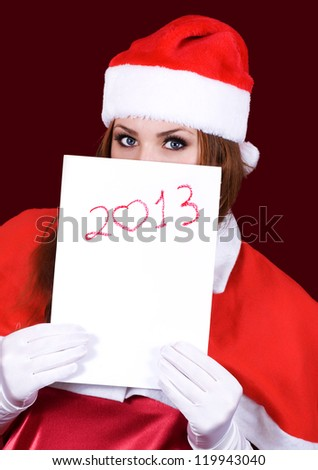 Girl in Santa's hat holding a sheet of paper with the inscription 2013 - stock photo