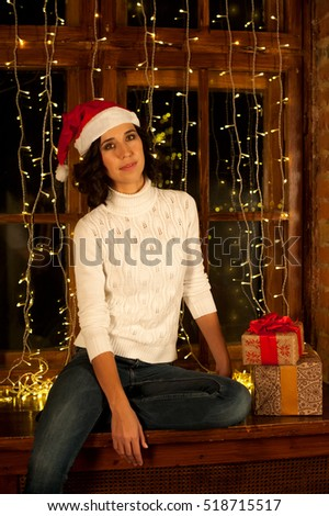 Girl in Santa's hat sits on a window decorated with a garland with Christmas gifts