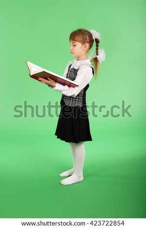 Girl in school uniform reading a book isolated on green - stock photo
