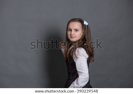 Girl in school uniform standing and writes on the Board - stock photo