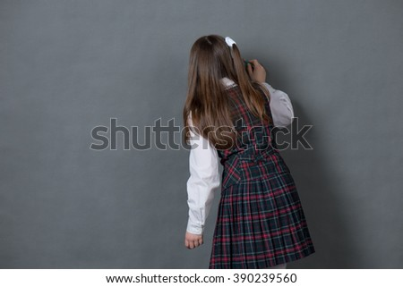 Girl in school uniform standing with his back and writes on the Board - stock photo