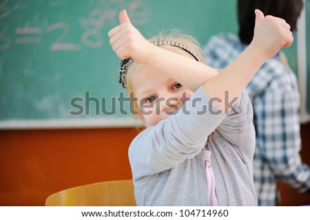 Girl in school with thumbs up - stock photo