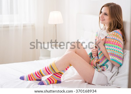 Girl in shawl sitting on a bed - stock photo