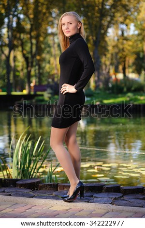 Girl in short black dress against the pond in the city-park