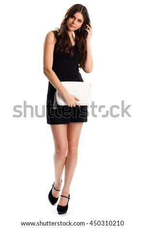 Girl in short black dress. Dark heel shoes and handbag. Elegant model on blank background. Expensive outfit with accessory.