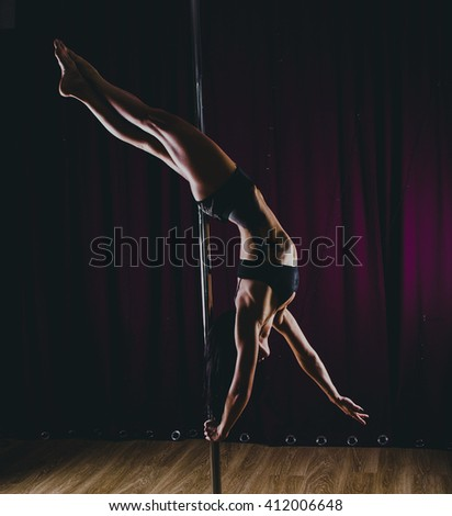Girl in short  top  and shorts  the pole dancing on dark light