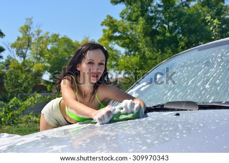 Girl in shorts and bathing suit wash the car on the street