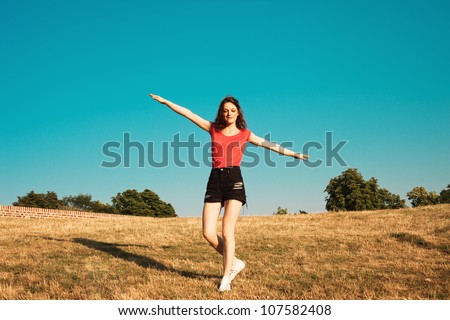 girl in shorts and t-shirt making balance on top of hill with eyes closed blue sky in background summer day - stock photo