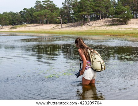 girl in shorts taking pictures of the water lilies in the lake
