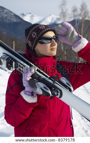 Girl in ski clothes taking skis on her shoulder is looking to the sun through her sun glasses - stock photo
