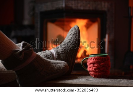 girl in slippers by the fire - stock photo