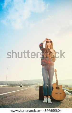 Girl in sneakers with a guitar in the road. Image effect sunlight - stock photo