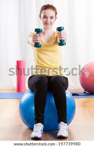 Girl in sportswear sitting on exercise ball and lifting weights - stock photo