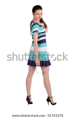 Girl in stripy blue dress stands turned around. Isolated on white.