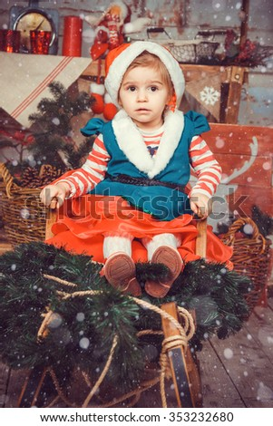 Girl in suit of Christmas elf sitting in a sled