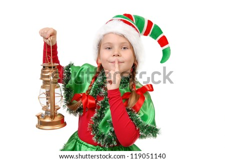 Girl in suit of Christmas elf with oil lamp with finger over her mouth. Isolated on a white - stock photo